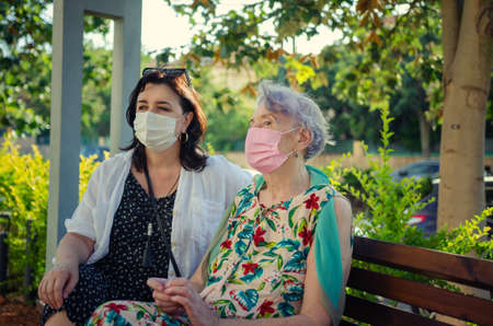 Companion or volunteer and a senior adult woman, wearing protective masks, sit on a park bench next to a house.