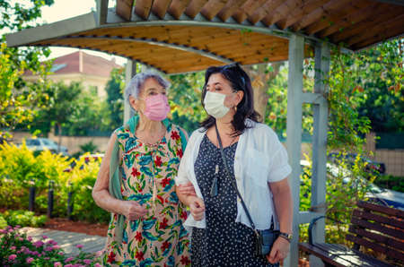 Companion or volunteer and a senior adult woman wearing a protective mask during coronavirus. They are walking in the park next to a house. Stock Photo