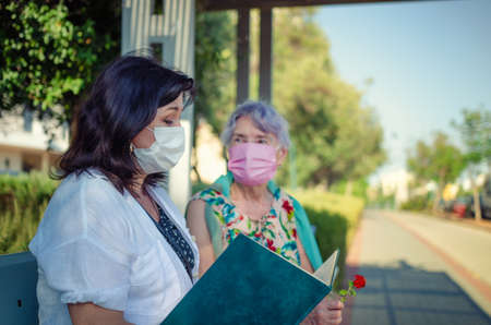 Day care provider reads a book to an elderly woman while sitting on a street bench during coronavirus. Both are wearing protective masks. The old lady's face is slightly blurred. Stock Photo