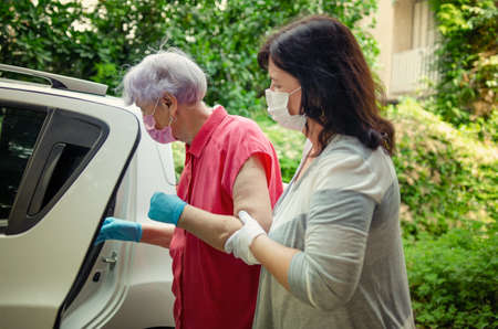 Carer escorting by car an elderly woman to medical or other appointments. Both wear protective masks.