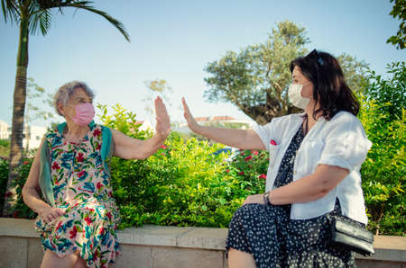 Carer and senior adult woman demonstrate air five gesture. Their palms do not touch. Their faces in protective masks as required during the pandemic