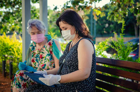 A kind volunteer teaches a senior adult woman how to enjoy a digital tablet. Both in protective face masks sitting on a park bench. Summer sunny day. Stock Photo