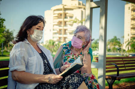 An elderly woman listens very carefully to a kind volunteer reading book aloud. It is providing emotional support for old people.  Both in protective face masks sitting on a park bench.