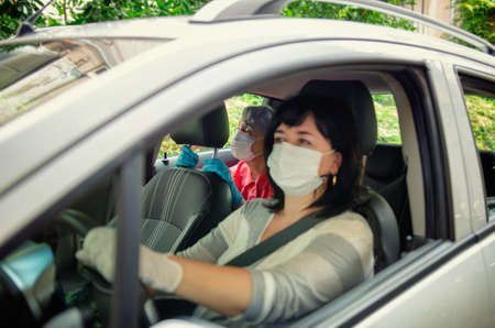 Carer drives a senior adult woman to planned outings or events. Both wear protective masks. The face of the caregiver is slightly blurred, the old lady is in focus. Stock Photo