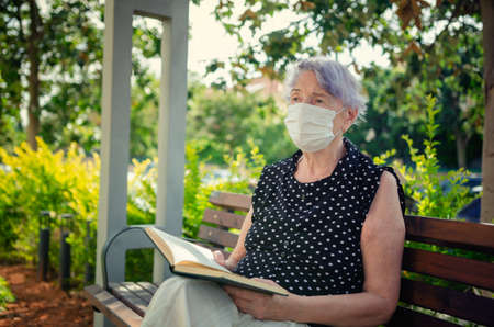 A lonely old woman in a white protective mask opened a book, but she cannot start to read. She is sad. Summer sunny day.