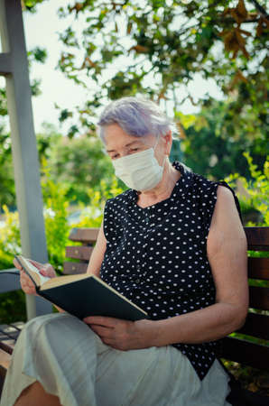 A senior adult woman in a protective mask reads a book very carefully on the street. She sits alone on the bench. Vertical portrait.