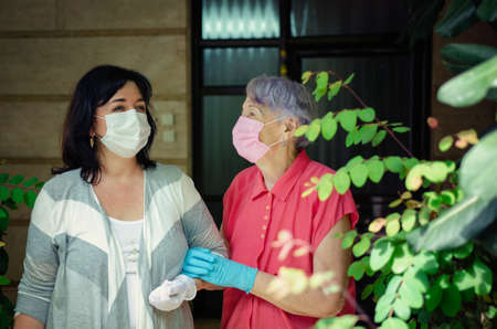The caregiver goes out daily with the elderly client strolling. Both in anti-virus masks and rubber gloves. Summer sunny day. Stock Photo