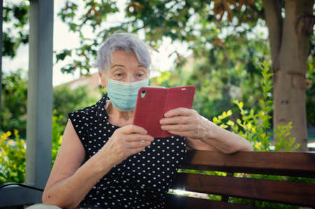 Surprised face of an elderly woman in a protective mask looking at the screen of a mobile phone. She sits on a wooden bench next to the house on a beautiful summer day.