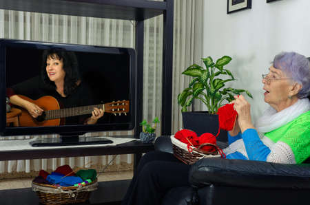 A lonely old woman loves to knit in front of a TV screen and watch retro channels. She often sings along with her favorite singers.