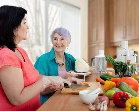 Female caregiver or volunteer and senior adult woman cook vegetable salad together. The old lady looks happy. Banque d'images
