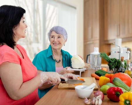 Female caregiver or volunteer and senior adult woman cook vegetable salad together. The old lady looks happy. Reklamní fotografie
