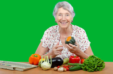 Cheerful senior adult vegetarian woman sits at a table with fresh vegetables and looks at the camera on green background.
