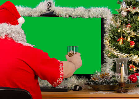 Santa Claus compliments everyone on Christmas Eve via the Internet. He raises a celebratory toast while looking at the chroma key computer screen.