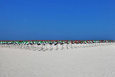 Installation in honor of the celebration of the UAE flag day. Many flags of red, green, white and black colors form a composition on clean light sand under a bright blue sky. They symbolize Arab unity.