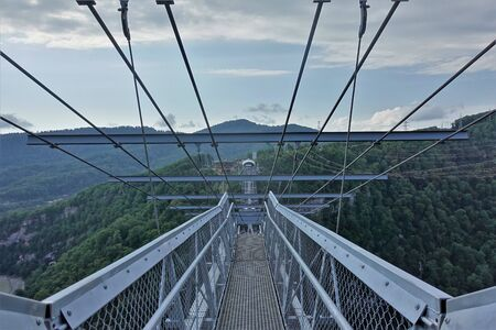 Skybridge is one of the longest suspension footbridges in the world. A bridge of metal and concrete over a deep gorge and river. Lattice floor and railings, magnificent views of the Caucasus Mountains. Standard-Bild