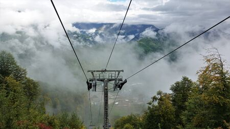 Cableway in the mountains of the Caucasus. Cabs fly right through very low white clouds. Visible mountains, yellow autumn leaves on the trees.