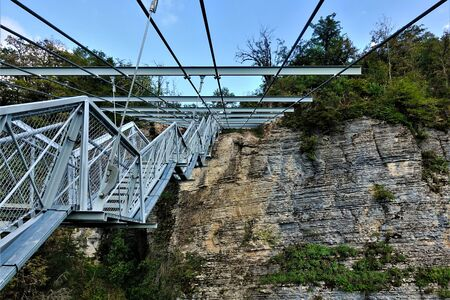 Skybridge in Sochi. Suspension bridge over the gorge. Made of metal and other modern materials. The bridge and railings are trellised. There are green plants on the rock. Standard-Bild