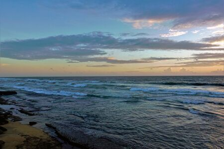 Sunset over the Indian Ocean. Turquoise waves run to the sandy shore. The rays of the setting sun painted the clouds in pink, gold, lilac, purple shades. Silence. Calm Relaxation. Banco de Imagens