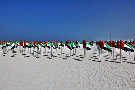 Celebrating the UAE State Flag Day. On the clean white sand of the beach, an installation of many flags of red-green-white-black colors. It is a symbol of Arab unity. Bright blue sky. Beautiful contrast of colors.
