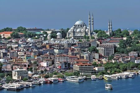 Panorama of the beautiful Istanbul. The Bosphorus Strait with many ships. The majestic mosque on the dais. Many closely standing modern residential buildings.