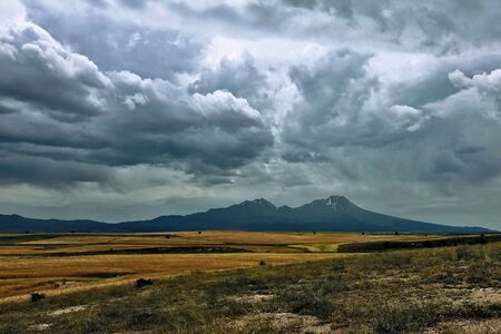 Storm clouds gather over the volcano. The beautiful Hassan volcano rises on the plain, next to the fields of wheat. Gloomy picturesque clouds hung over the top of the mountain. Alarming