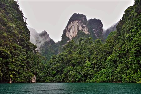 Unique Cheo Lan Lake on a rainy day. On the emerald water of the lake, ripples from raindrops. On the shore there are unusual high cliffs covered with lush tropical vegetation. The fog hides the peaks of the mountains. Mysteriously.