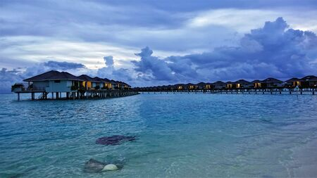 Evening in the Maldives. Dusk. Picturesque clouds on the sky. In water villas a light came on. The aquamarine ocean is calm and transparent. Large mantas swim along the coast in shallow water. Silence. Peace. Standard-Bild