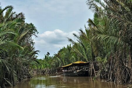 Mekong Delta. In a narrow branch of the river, on calm dark water, there is an exotic ship with a yellow roof. On the banks of impassable thickets of palm trees. Blue sky with light clouds. Vietnam. Stock fotó