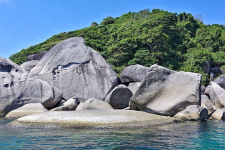 Amazing Similan island. On the shores of the turquoise sea lie huge ancient smooth boulders. Behind them rises a hill overgrown with dense tropical forest. Bright blue sky, sunny day. Thailand.