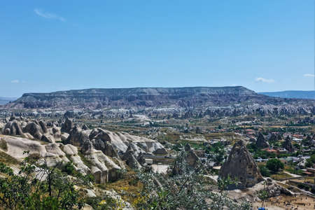 Panorama of amazing Cappadocia. Against the blue sky, a beautiful mountain with a wide flat top. In the foreground are pointed cliffs with caves inside. In the valley and between the rocks are residential buildings. Turkey 스톡 콘텐츠