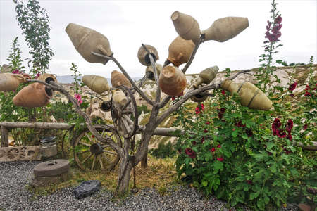 Pigeon Valley in Cappadocia. Clay pots and old wooden wheels hang on the branches of a dry tree. Mallows are blooming nearby. Amazing white cliffs are visible behind the wooden fence.