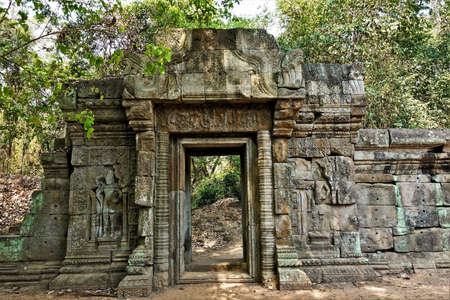 The wall of the ancient castle is dilapidated. On the stones are bas-reliefs, carvings, ornaments. The doorway is preserved, this is the passage from the jungle to the jungle. This is the memory of a vanished civilization. Cambodia, Angkor
