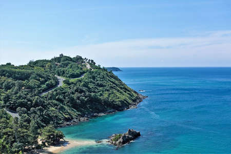 Top view of a large green island with a dense forest. Sunny summer day, blue sky. In a calm aquamarine sea, a small rocky islet and a strip of sandy beach. Thailand. Phuket