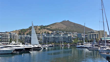 Sunny summer day. On the calm water of the bay are yachts and sailboats. Residential buildings on the shore. Against a clear blue sky, Signal Hill is visible. Cape Town South Africa.