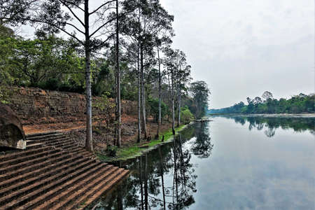 Calm river in ancient Angkor. Stone steps descend from the ruins of a brick wall to the water. On the banks of trees grow. Reflection in water. Cambodia