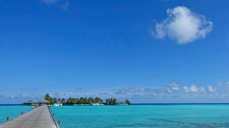 Delightful Maldivian picture. There is a wooden footpath over the aquamarine ocean. Ahead is an island with awnings, palm trees, a pier. Boats near the shore. There are light clouds in the azure sky.