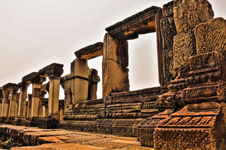 Ruins of the famous ancient Angkor. At the top of the temple there is a dilapidated colonnade. The stones are decorated with carvings, ornaments. Empty window openings look up to the sky. Cambodia. Foto de archivo