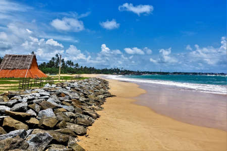 Summer, beach, ocean. Aquamarine waves leave a white foam on the yellow sand. Stones lie along the shore, and there is a red wooden hut. Silhouettes of palm trees against the blue cloudy sky.Sri Lanka