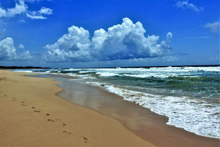 Tropical beach. Indian Ocean coast. Turquoise waves roll ashore, on the yellow sand openwork white foam, footprints. There are picturesque clouds in the blue sky. Sri Lanka. Imagens