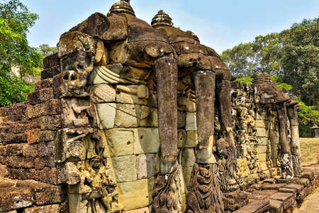 Unique Angkor. Terrace of elephants. On a stone pedestal, there are sculptures of elephant heads with long trunks. Decorated with carvings, ornaments. There are bas-reliefs on the dilapidated wall. Editorial