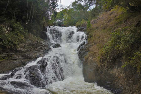 Between the mountain slopes a waterfall rages and foams on the stones. Tropical trees grow around. Vietnam. Dalat.