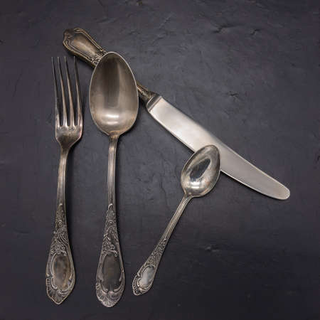 A set of cutlery from cupronickel: table and teaspoon, fork, knife. Everything was produced at the beginning of the 20th century, more than 100 years ago, covered with a patina. The background is blac