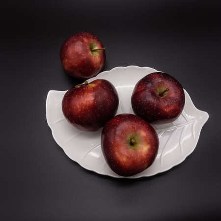Three ripe red apples lie on a white plate in the form of a leaf. There is another one nearby. Black background. Color contrast. View from above. 版權商用圖片