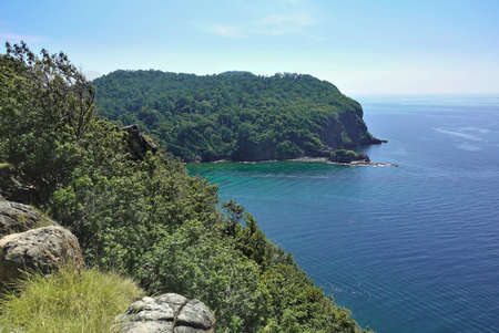 In the foreground is a mountain slope with large stones. A green island is visible in the turquoise Andaman Sea. Clear azure sky. Thailand. Summer.