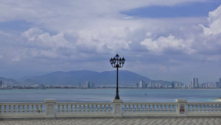 The embankment is surrounded by a white balustrade. In the center there is a lamp in the form of antique lanterns. City buildings and mountains are visible beyond the bay. Blue sky, clouds. Vietnam.