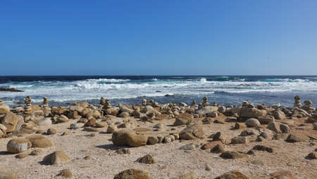 The turquoise waves of the Atlantic Ocean roll ashore. White foam. Many rounded stones are stacked in pyramids. On two boulders there is a seating board. Cape of Good Hope. South Africa.