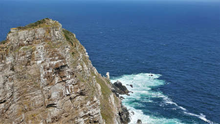 The sheer rocky slopes of Cape Point set against the blue Atlantic Ocean. There is a tiny house at the top of the cliff. At the foot of the white foam of the waves. South Africa.