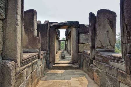 A dilapidated stone corridor at the top of the temple. Doorways, windows, columns are damaged by time. There is no roof. Sunny day. Cambodia. Angkor. Unesco heritage.