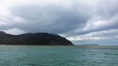 There are small waves on the turquoise Atlantic Ocean. The peaks of the mountains on the coast are hidden in low clouds. Blue sky in the distance. South Africa. Reklamní fotografie