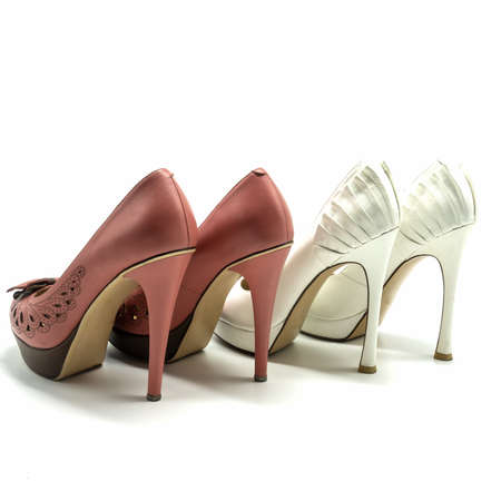 Two pairs of women's high heels and platform shoes. Made of genuine leather in white and pink. Decorated with embroidery, slits, folds. Back and side views. Isolated over white background.
